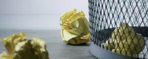 Papierkorb mit gelben zerknüllten Notiztellten